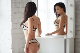 Woman in bra and underwear staring in the mirror
