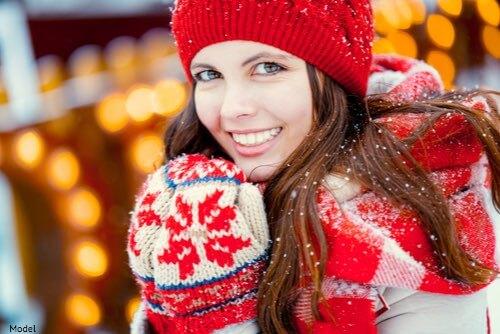 Woman smiling wearing mittens