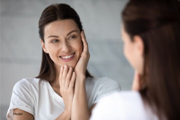 Woman starring in the mirror smiling