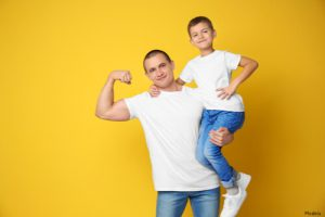 Dad flexing his bicep while holding his son